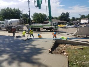 Longs Peak Middle School front entry concrete being installed by workers