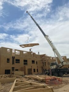crane bringing in framing to upper story on partially completed building