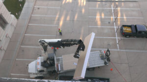 View from top of roof looking down over parking lot with crane truck bringing up construction materials
